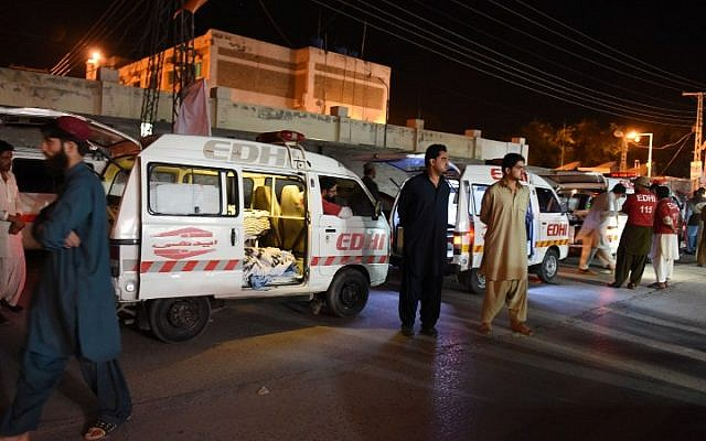 Residents gather around an ambulance carrying dead bodies of killed bus passengers outside the hospital in Quetta on May 30, 2015, after unidentified gunmen stormed passenger buses in southwest Pakistan, killing at least 19 people, officials said. The buses were enroute to the port city of Karachi when they were attacked in Mastung district, according to Akbar Harifal, deputy district commissioner. (AFP PHOTO / Banaras KHAN)