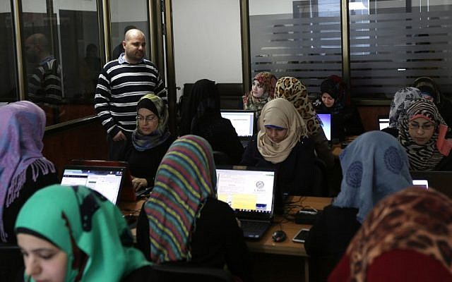 Illustrative: Workers doing data entry at the offices of Unit One in Gaza City (Mahmud Hams / AFP)