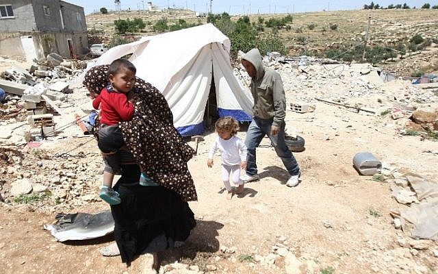 A Palestinian family whose house was demolished by Israeli bulldozers walk past a tent on April 21, 2015, in the southern West Bank village of Ad-Deirat Rifaiyya. (Hazem Bader/AFP)