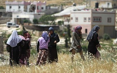 Palestinian women walk in a field on April 21, 2015 in the West Bank village of Ad-Deirat Rifaiyya, where more than half of the homes are built on land owned by the villagers but without Israel's approval leaving them under threat of demolition by Israeli bulldozers. (Photo credit: Hazem Bader/AFP)