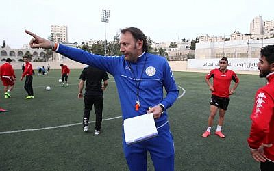 Ahli al-Khalil football club's coach, Italian Stefano Cusin gestures to his players during a training session on April 24, 2015 in the West Bank town of Hebron. A Palestinian football club from the southern West Bank is hoping that the turnaround led by a new coach from Italy could see it reaching a top pan-Asian championship. (photo credit: AFP PHOTO / HAZEM BADER)