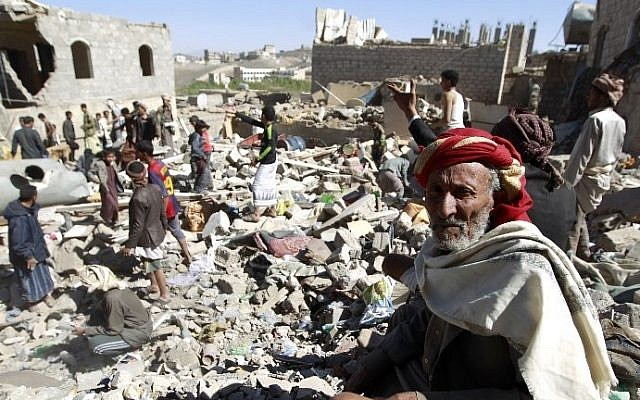 A Yemeni man sits on the rubble as people search for suvivors in houses destroyed by an overnight Saudi-led air strike on a residential area in Yemen's capital, Sanaa, on May 1, 2015. (photo credit: AFP/MOHAMMED HUWAIS)