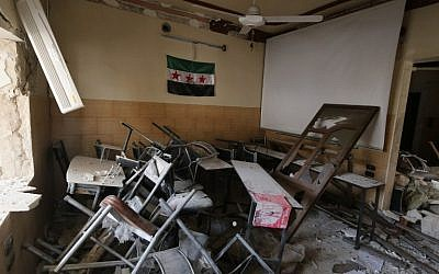 A pre-Baath Syrian flag, now used by the Syrian opposition, hangs in a heavily damaged classroom after a barrel bomb hit a school in Syria's northern city of Aleppo Saif al-Dawla district, where control is split between the Syrian regime and opposition, on May 3, 2015.  (AFP PHOTO / BARAA AL-HALABI)