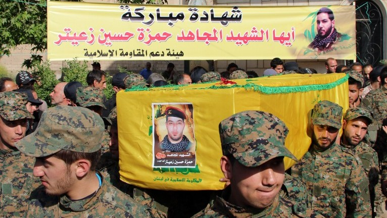 """Hezbollah fighters carry the coffin of fellow Shiite militant Hamza Hussein Zeiter during his funeral on May 5, 2015 in the town of Baalbek in eastern Lebanon's Bekaa Valley. The Hezbollah fighter was killed during clashes with members of Al-Nusra Front, Al-Qaeda's Syrian wing, in the Syrian region of Qalamoun. The banner by the association of the support to the Islamic Resistance reads in Arabic """"Blessed martyrdom to the martyr Jihadi Hamza Hussein Zeiter"""". (Photo credit: AFP)"""