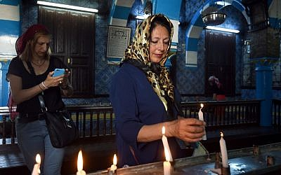 A Jewish woman lights a candle at the Ghriba synagogue on the Tunisian resort island of Djerba on May 6, 2015, at the start of a two-day annual pilgrimage. (photo credit: AFP PHOTO / FETHI BELAID)