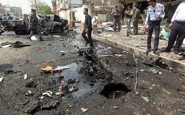 Iraqi security forces inspect the scene of a car-bomb blast targeting Shiite pilgrims on an annual march to a Baghdad shrine on May 9, 2015. (AFP/Ahmad al-Rubaye)
