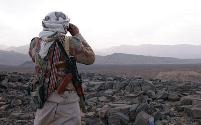 An armed Yemeni tribesman from the Popular Resistance Committees supporting forces loyal to Yemen's Saudi-backed fugitive President Abedrabbo Mansour Hadi looks through binoculars as they continue to battle Shiite Houthi rebels in the area of Jaadan, in Marib province east of the capital, Sanaa, on May 9, 2015. (photo credit: AFP/STR)