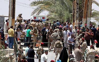 Iraqi security forces stand guard as residents from the city of Ramadi, who fled their homes to escape  an advance by Islamic State group forces, wait to cross Bzeibez bridge, May 16, 2015 (AFP/ SABAH ARAR)