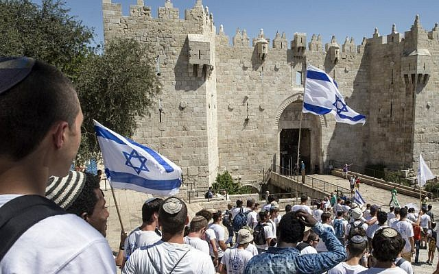 """Israeli youth hold their national flag as they take part in the """"flag march"""" through Damascus Gate in Jerusalem's Old City during celebrations for Jerusalem Day on May 17, 2015. (AFP Photo/Jack Guez)"""