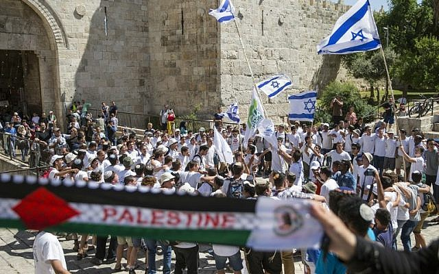 "Palestinian women hold a scarf bearing the Palestine name as Israeli youths carry their national flag in the ""flag march"" through Damascus Gate in Jerusalem's Old City during celebrations for Jerusalem Day on May 17, 2015. (AFP Photo/Jack Guez)"