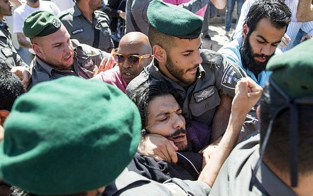 """Palestinian demonstrators clash with Israeli police during the """"flag march"""" through Damascus Gate in Jerusalem's Old City during celebrations for Jerusalem Day on May 17, 2015. (AFP Photo/Jack Guez)"""