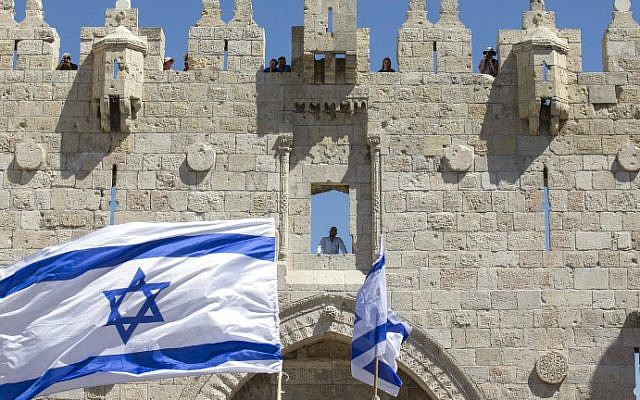 """Israeli youth wave the nation's flag in the """"flag march"""" through Damascus Gate in Jerusalem's Old City during celebrations for Jerusalem Day on May 17, 2015. (AFP Photo/Jack Guez)"""