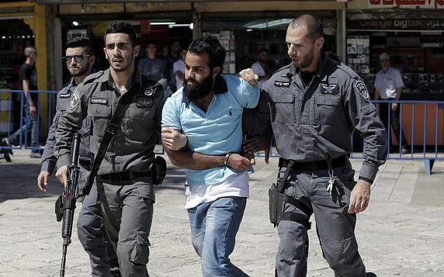 """A Palestinian demonstrator is detained by Israeli police during the """"flag march"""" through Damascus Gate in Jerusalem's Old City during celebrations for Jerusalem Day on May 17, 2015. (AFP Photo/Jack Guez)"""