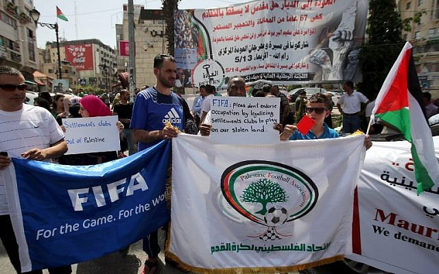 Palestinians hold banners as they demonstrate in the center of Ramallah, demanding the suspension of Israel from FIFA, May 20, 2015. (AFP/Abbas Momani)