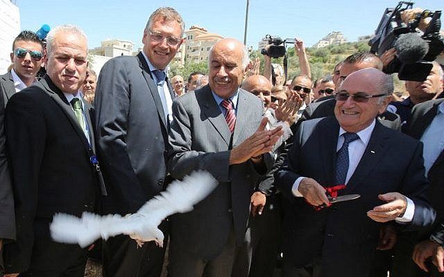 FIFA president Joseph Blatter, right, releases a dove as Palestine Football Association President Jibril Rajoub, center, claps during his visit to the village of Dura al-Qaraa, near the West Bank city of Ramallah, on May 20, 2015. (AFP/ABBAS MOMANI)