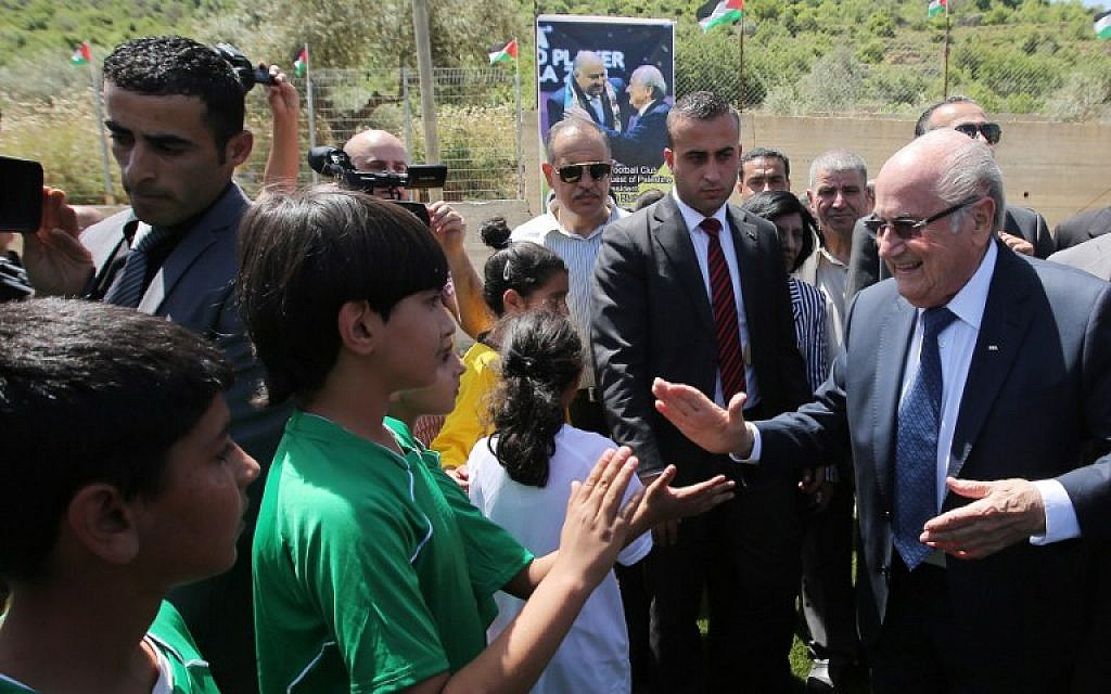 FIFA president Joseph Blatter (R) shakes hands with Palestinian children during his visit to the sports club in the village of Dura al-Qaraa, near the West Bank city of Ramallah, on May 20, 2015.  (AFP PHOTO / ABBAS MOMANI)
