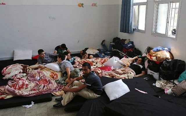 Palestinian refugees from Syria's Yarmouk refugee camp sit on mattresses inside a school as they prepare for their official exams for the 9th grade in the capital Damascus, on May 20, 2015. (AFP/Youssef Karwashan)