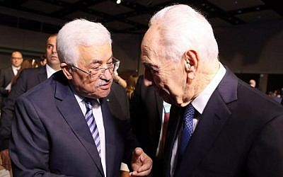 Former president Shimon Peres (right) shakes hands with Palestinian Authority President Mahmoud Abbas (left) on the opening day of the World Economic Forum on the Middle East and North Africa 2015, taking place in the Dead Sea resort of Shuneh, Jordan, on May 22, 2015. (AFP/Khalil Mazraawi)