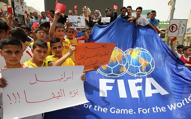 Palestinian youth hold red cards and placards reading in Arabic, 'Israel out of FIFA,' during a demonstration against the Israel Football Federation in the West Bank city of Hebron, on May 28, 2015. (AFP photo/Hazem Bader)