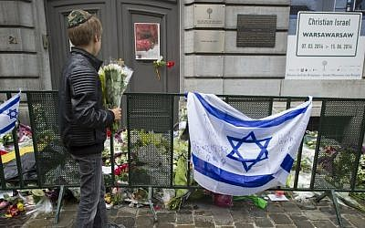 A Jewish boy standing with flowers in front of an Israeli flag and flowers laid outside the Jewish Museum in Brussels, where a deadly shooting took place two days before, May 26, 2014. (AFP/BELGA/ANTHONY DEHEZ)
