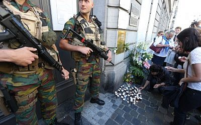 People lay down candles as soldiers stand guard at the entrance of the Jewish museum in Brussels, on 24, May 2015. (Nicolas Maeterlinck/AFP)