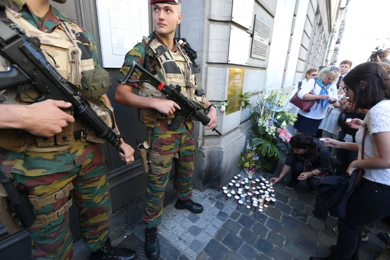 People lay down candles as soldiers stand guard at the entrance of the Jewish museum in Brussels, on May 24, 2015. (Nicolas Maeterlinck/AFP)