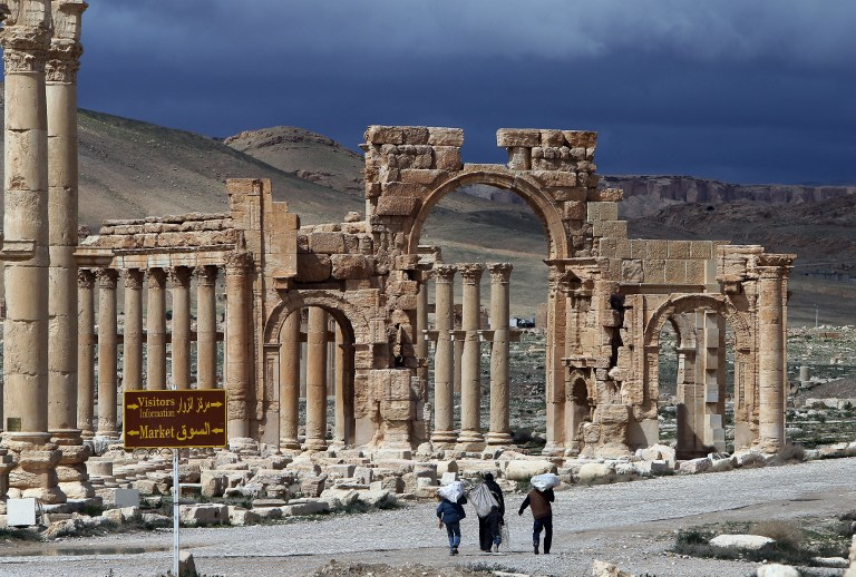 Syrians walking in the ancient oasis city of Palmyra on March 14, 2014. (AFP/Joseph Eid)