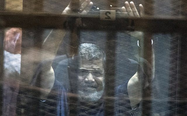 Egypt's deposed Islamist president Mohammed Morsi raises his hands from behind the defendant's cage as the judge reads out his verdict sentencing him and more than 100 other defendants to death, at the police academy in Cairo on May 16, 2015. (Khaled Desouki/AFP)