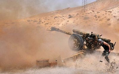 File: A Syrian army soldier fires artillery shells towards Islamic State (IS) jihadists in northeastern Palmyra on May 17, 2015. (AFP/STR)