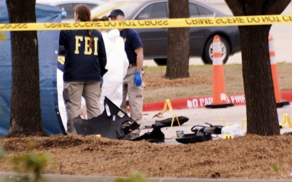 """An FBI agent views the area where debris of a car was blown up by police as a precaution, near the Curtis Culwell Center on May 4, 2015 in Garland,Texas after a shooting occurred during the """"Muhammad Art Exhibit and Cartoon Contest."""" (Photo credit: AFP /JARED L.CHRISTOPHER)"""