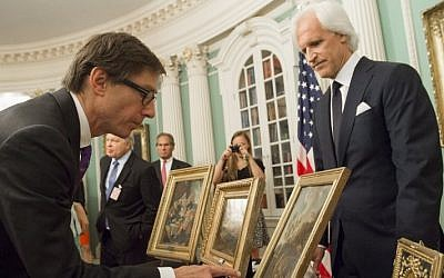 Germany's Ambassador to the US Peter Wittig (L), looks at five paintings that were to be returned to Germany in cooperation with the Monuments Men Foundation, during a ceremony at the State Department in Washington, DC, May 5, 2015. (AFP/SAUL LOEB)