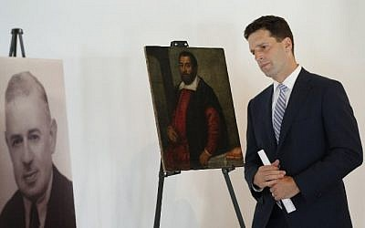 Benjamin M. Lawsky, superintendent at the New York State Department of Financial Services, examines the painting 'Portrait of a Man,' lost as a result of Nazi persecution and returned to its rightful heir, at the Museum of Jewish Heritage, New York, May 5, 2015. (photo credit: AFP/Eduardo Munoz Alvarez)