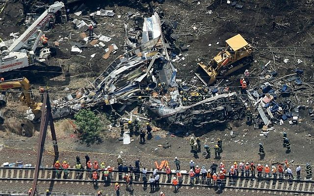 Investigators and first responders work near the wreckage of Amtrak Northeast Regional Train 188, from Washington to New York, that derailed yesterday May 13, 2015 in north Philadelphia, Pennsylvania. (photo credit: Win McNamee/Getty Images/AFP)