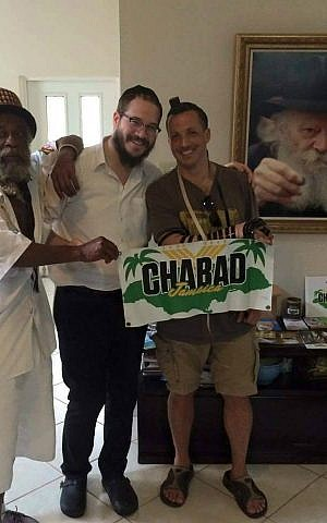 Rabbi Yaakov Raskin (center) instructs men on how to put on tefillin at Chabad House in Montego Bay, Jamaica. (Courtesy)