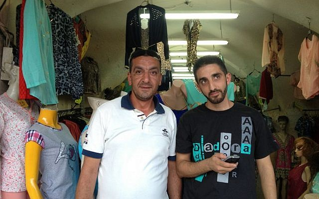 Ahmad al-Dabbagh, left, stands in front of a clothing shop in the Muslim Quarter that decided to remain open in defiance of police instructions (Elhanan Miller/Times of Israel)