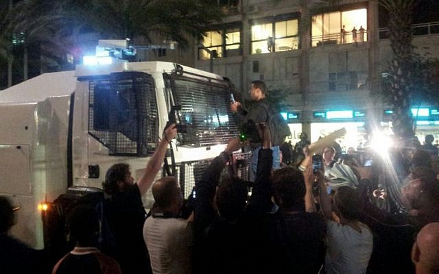 Protesters surround a water cannon truck in Tel Aviv. May 3, 2015 (photo credit: Judah Ari Gross/Times of Israel)