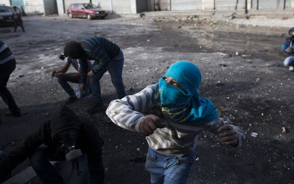 Palestinian youth throw stones during clashes with Border Police in the Shuafat refugee camp in Jerusalem following Friday prayers on November 7, 2014. (Yonatan Sindel/Flash90)