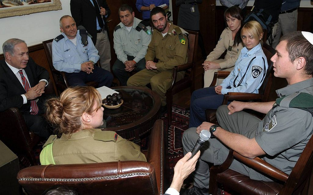 Benjamin Netanyahu, left, and then-IDF Chief Education Officer Brig. Gen. Eli Schermeister, second left, along with an education corps officer, back to camera, and potential converts on December 15, 2010 (Amos Ben-Gershom/ GPO/ courtesy)
