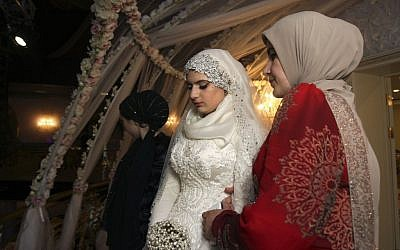 Chechen Kheda Goilabiyeva, second right, stands after her wedding with Chechen police officer Nazhud Guchigov, in Chechnya's provincial capital Grozny, Russia, Saturday, May 16, 2015. (AP Photo)