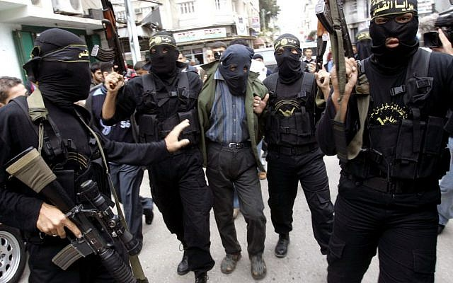 Palestinian Islamic Jihad masked gunmen hold up their guns as they display one of two men whom they alleged were Palestinian collaborators for Israel, in Gaza City, November 5, 2006. (AP/Khalil Hamra/File)