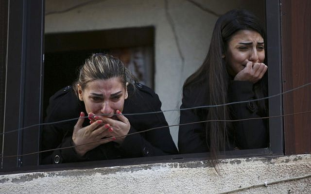 Two Alawite women mourn as they look from a window during the funeral procession of those who were killed in an overnight suicide bombing perpetrated by Al-Nusra Front at a coffee shop in the northern port city of Tripoli, Lebanon, Sunday, Jan. 11, 2015 (AP/Hussein Malla)