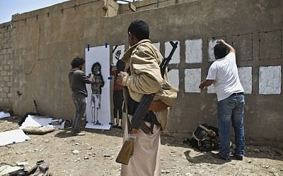 An armed man looks at graffiti artists spraying on a wall to commemorate the victims who were killed in Saudi-led coalition airstrikes in Sanaa, Yemen, Monday, May 18, 2015. (AP Photo/Hani Mohammed)