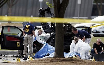 FBI crime scene investigators document the area around two deceased gunmen and their vehicle outside the Curtis Culwell Center in Garland, Texas, Monday, May 4, 2015. (Photo credit: AP/Brandon Wade)