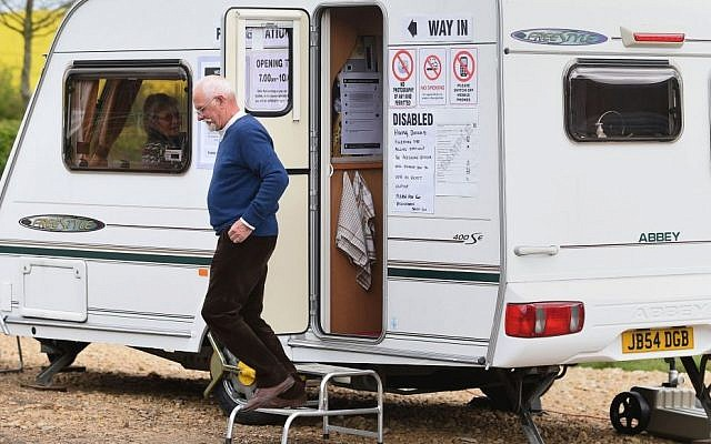 A man leaves after casting his vote in a caravan used as a polling station on Grange Farm in Garthorpe, England, Thursday May 7, 2015  (photo credit: Joe Giddens / PA via AP)