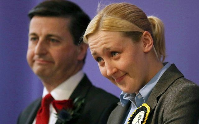 Paisley and Renfrewshire South constituency winner Mhairi Black of the Scottish National Party (SNP) and Labour's Douglas Alexander react at the Lagoon Leisure Centre in Paisley, Scotland, Friday May 8, 2015. Black, a 20-year-old student, becomes Britain's youngest lawmaker since the 17th century. (David Cheskin/PA via AP)