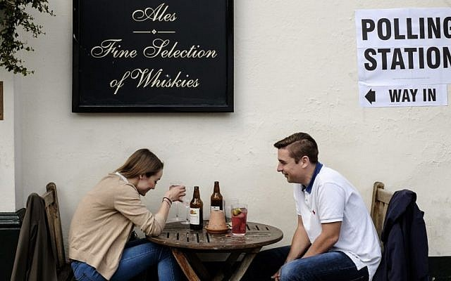 Patrons sit outside a pub, which is also serving as a polling station, in the borough of Kensington, London, May 7, 2015. (photo credit: AP/David Azia)