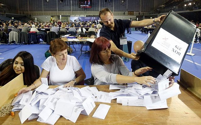 The first votes arrive at the general election count for the Glasgow constituencies at the Emirates Arena in Glasgow, Scotland, May 7, 2015. (photo credit: Danny Lawson/PA via AP)