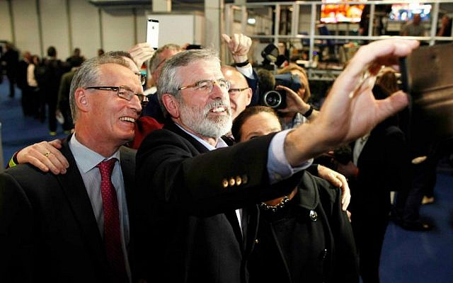Sinn Fein President Gerry Adams, right, and Sinn Fein candidate for North Belfast Gerry Kelly take a selfie at the Kings Hall count center, Northern Ireland, Friday, May 8, 2015. (AP Photo/Peter Morrison)