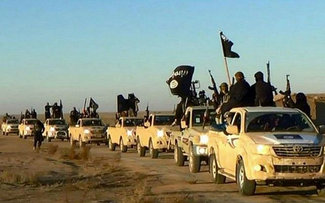 Undated file photo of Islamic State fighters holding up their weapons and waving flags in their convey of vehicles on a road leading to Iraq from Raqqa, Syria. (Jihadist website via AP)