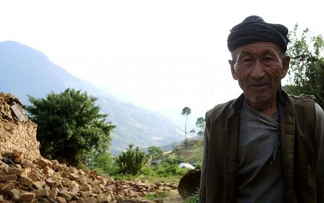 An elderly man smiles at passing aid workers in rural Nepal's Sindhupalchok district, a week after the first earthquake. (photo credit: Melanie Lidman/Times of Israel)